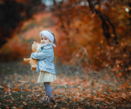 Young girl holding teddy bear dressed in coat and hat in woods - feature