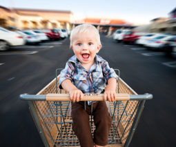 Toddler boy sitting in supermarket trolley in car park - feature