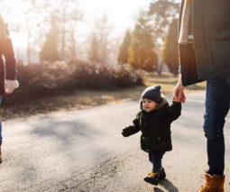Toddler walking with parents in beanie and coat cold - feature