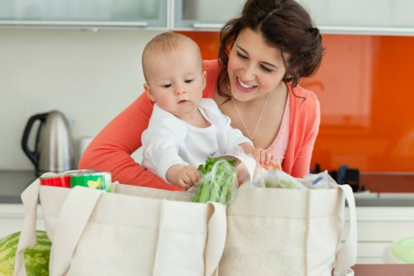woman holding baby unloading groceries
