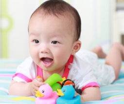 Smiling Asian baby on tummy with toys