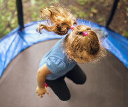 Young girl jumping on a trampoline - feature