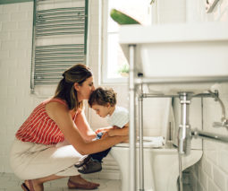 Mother helping toddler boy on toilet training - feature