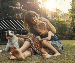 Mum with two children and dog outside by the trampoline