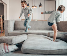 Two boys playing on couch with cushions - feature