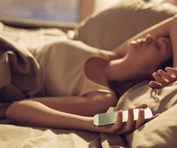 Woman in bed with her mobile phone - feature