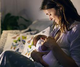 Mother breastfeeding baby at night - thumbnail