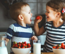 Brither and sister sharing strawberries