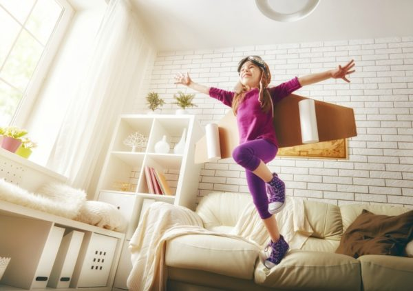 little girl jumping off lounge with cardboard wings