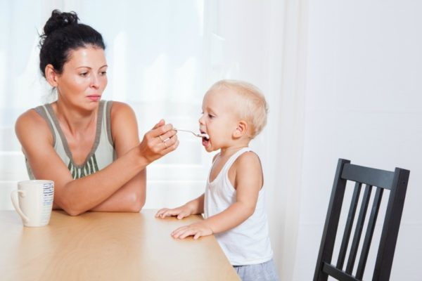 mother feeding toddler at table