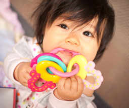Baby chewing on teething toy - feature