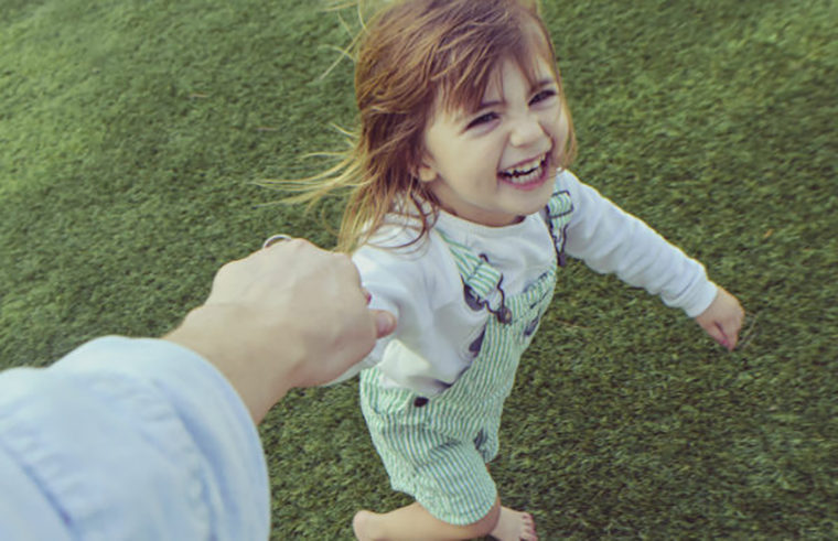 Toddler girl running on grass holding parent's hand - feature