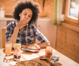 Woman feeling sick at kitchen table - feature