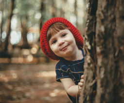 Young girl wearing a red beanie hiding behind tree - feature