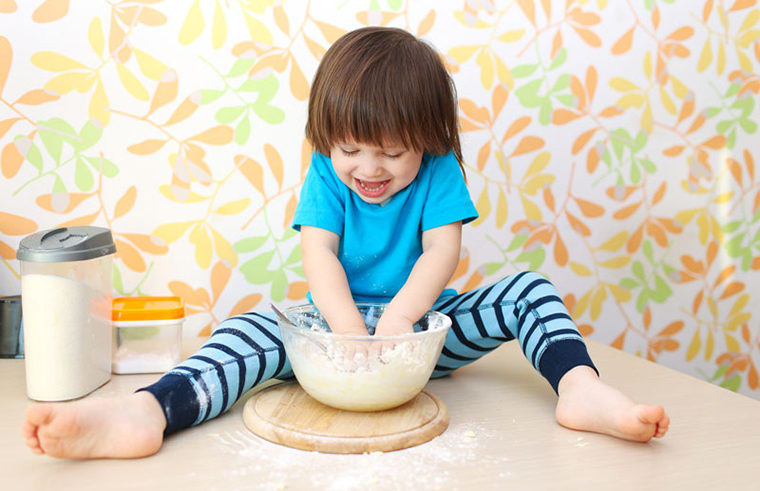 Boy sitting on kitchen bench cooking mess -feature