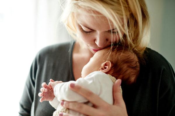 Mother kissing newborn's head