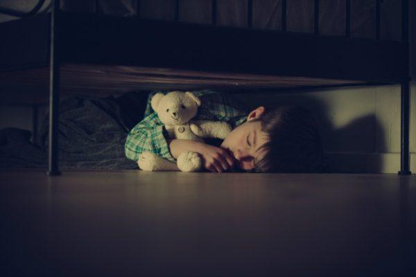 scared child asleep under bed
