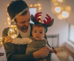 Baby with reindeer headband looking at Christmas lights - feature