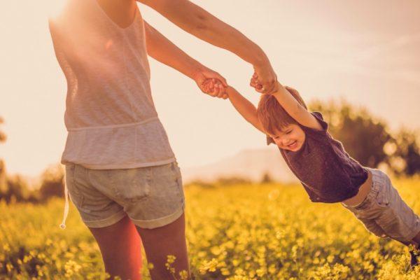 mum swinging child in field