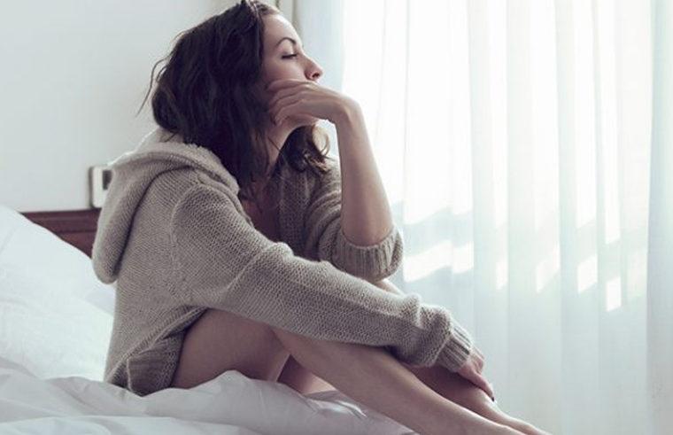 Sad woman sitting on bed feeling depressed