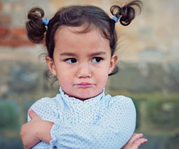 Toddler girl with arms crossed looking angry - feature