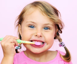 Young girl in pink brushing teeth - feature