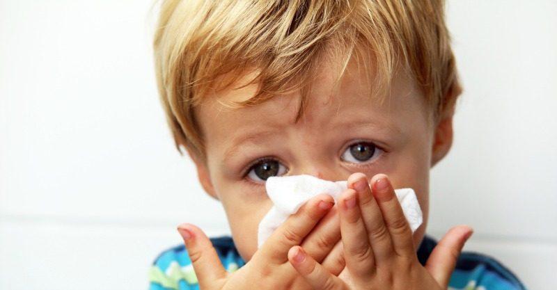 little boy blowing nose