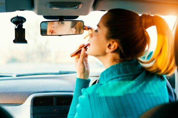 woman doing makeup in car