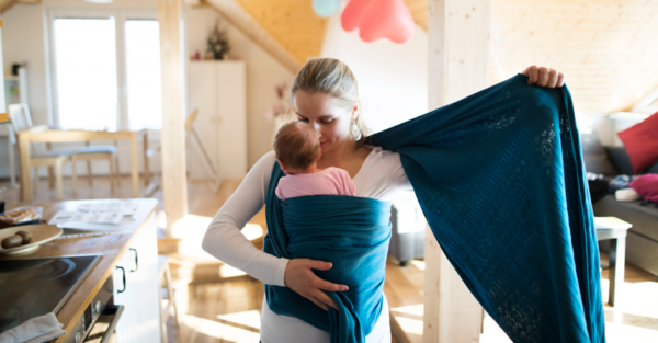 Mother placing baby in sling