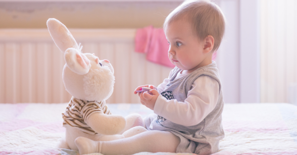 Baby sitting on bed with toy