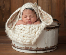 Baby boy asleep in bucket with knitted Easter bunny beanie on their head - feature