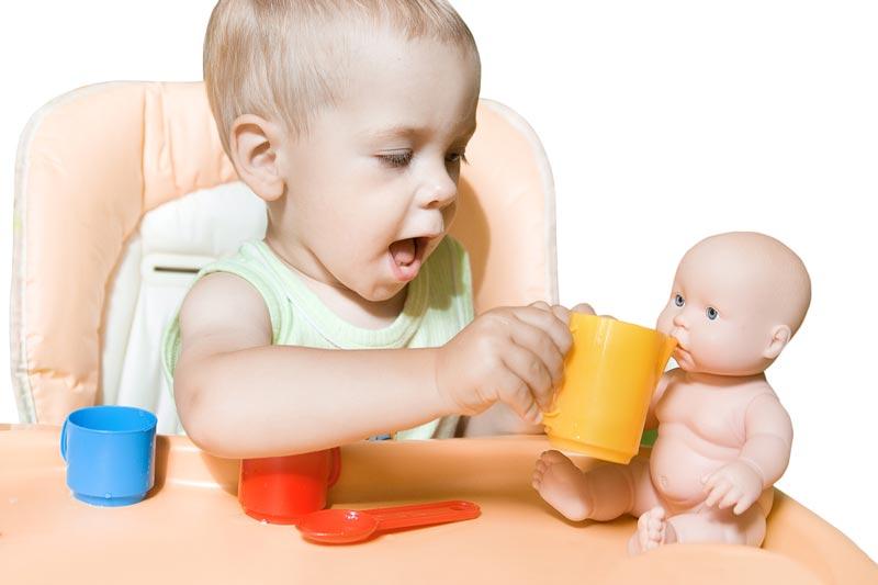 Boy feeding doll