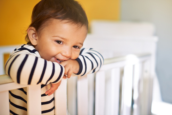 Cropped shot of an adorable baby girl standing in her crib at home