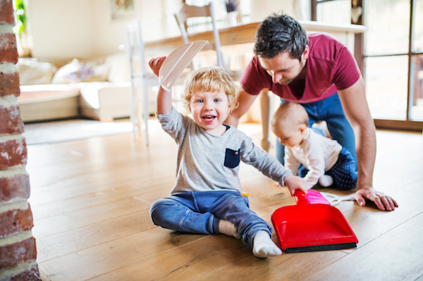 Dad cleaning with toddler and baby