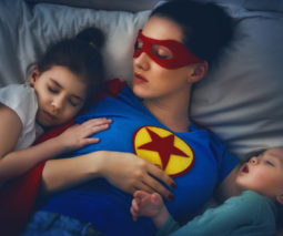 Mother in superhero costume asleep on bed with child and baby