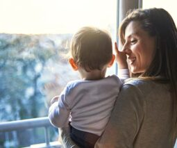 Mum with toddler looking out window