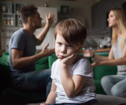 Young boy sitting in front of parents fighting arguing - feature