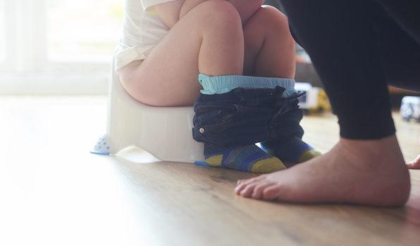 Boy toilet training on potty