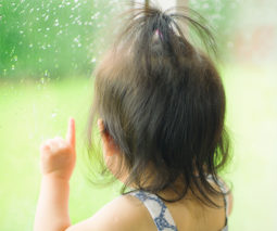 Baby looking out window at rain- feature
