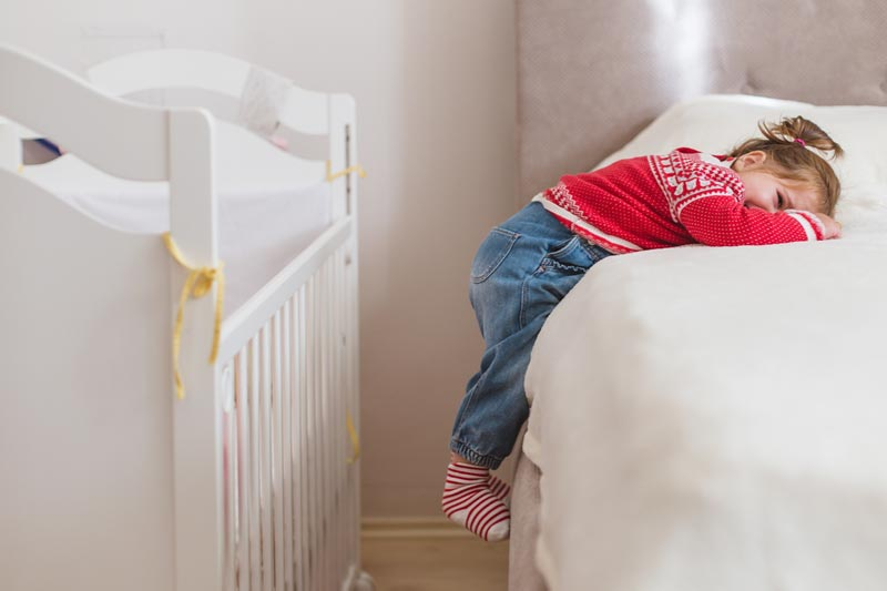 Toddler girl lying on bed next to cot