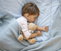 Toddler boy asleep in bed holding teddy - feature