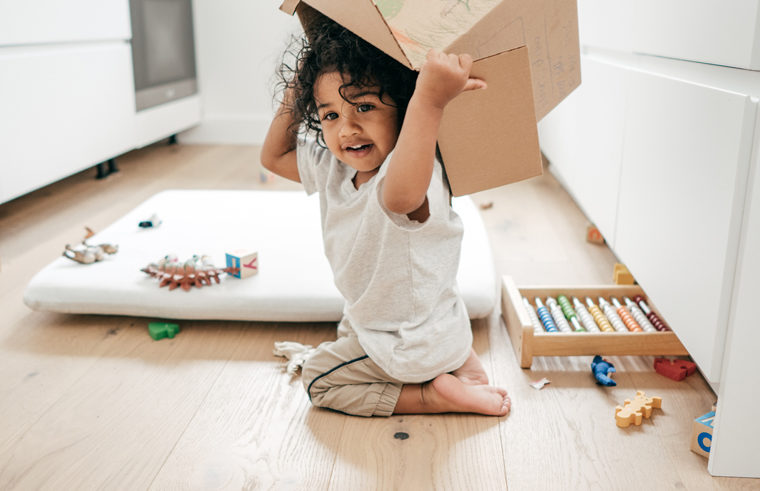 Toddler playing with a box surrounded by toys
