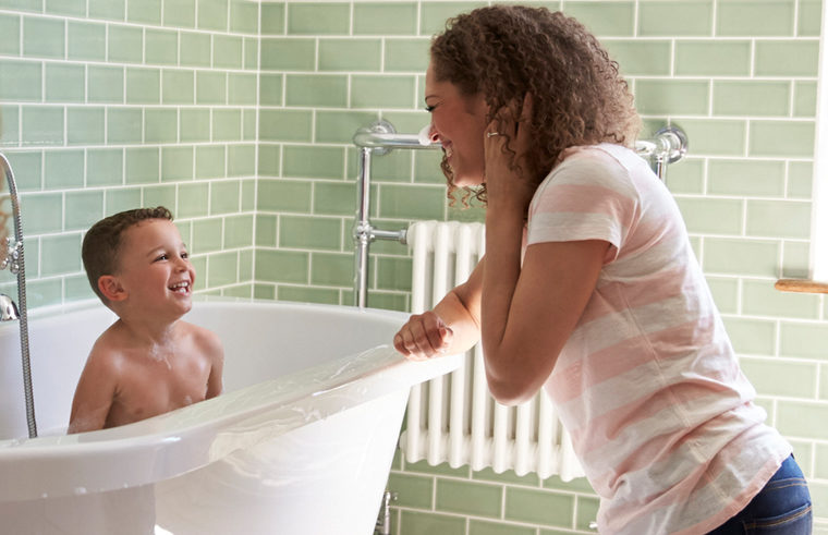 Prechool aged boy laughing in the bath with mum watching