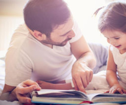 Father reading a book with toddler girl - feature