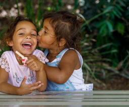 Two happy Aboriginal girls eating ice cream - feature