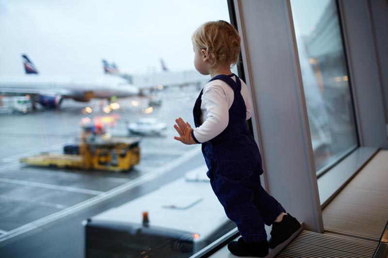 Toddler looking at airplanes at airport
