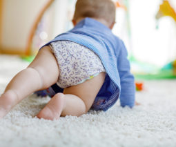 Baby girl crawling on rug - feature