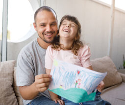 Father and daughter laughing on a couch with card or drawing - feature