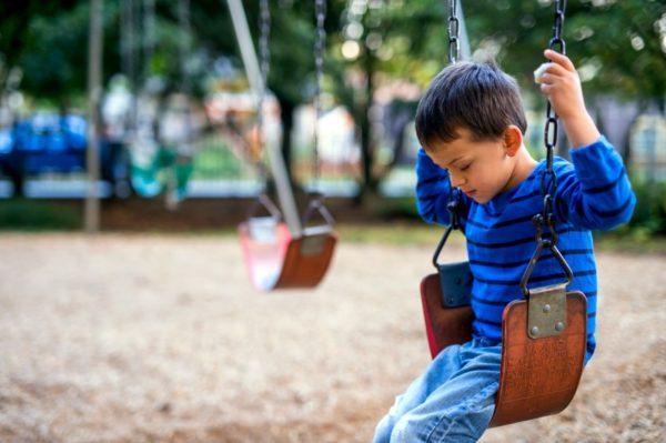 Sad boy on swing