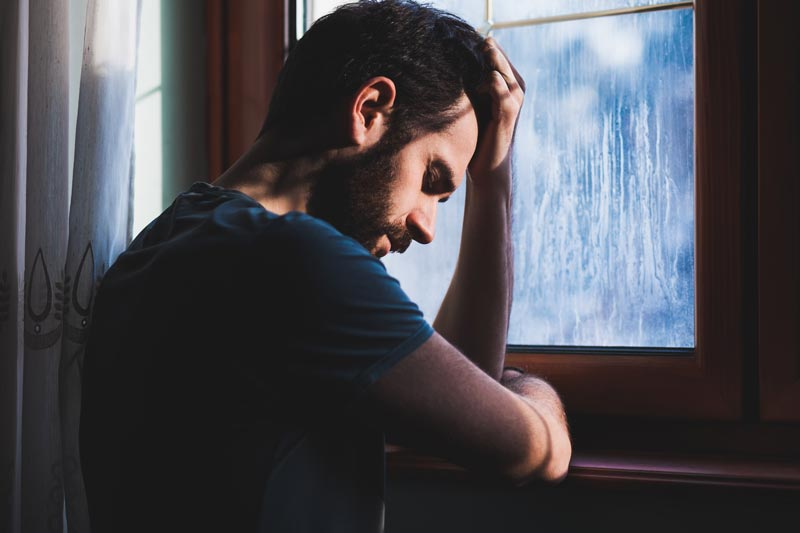 Tired man standing at window